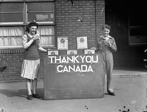"A young boy and girl standing, holding milk, standing next to a stand that says ""Thank you Canada"""